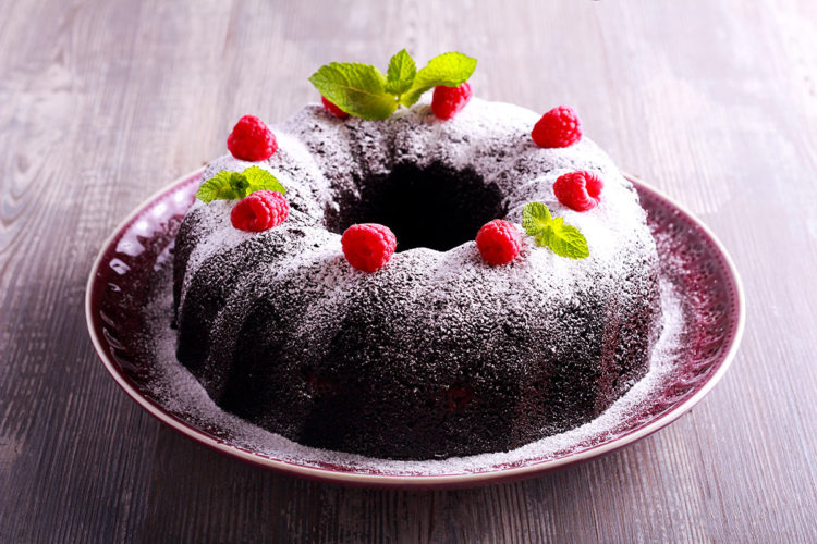 chocolate cake topped with powdered sugar and raspberries